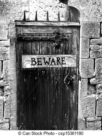 Pictures of beware sign on an old wooden gate with spikes.