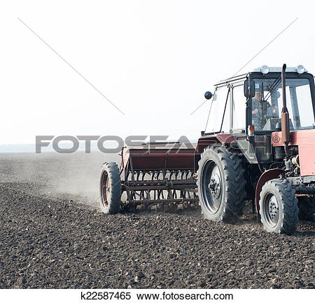 Stock Image of tractor and seeder planting crops on a field.