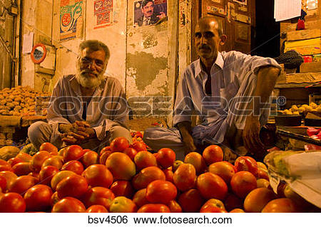 Stock Images of Two shopkeepers selling tomatoes at night in the.