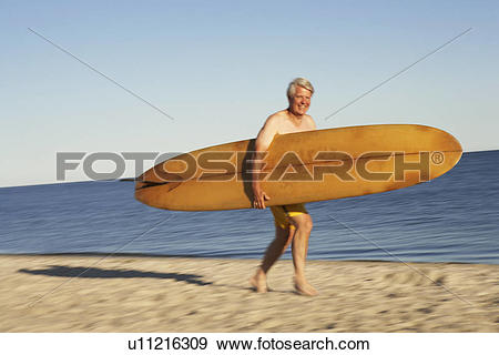 Stock Photograph of Portrait of a mature man holding a surfboard.