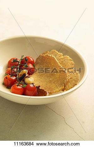 Stock Photo of Roasted tomatoes and toasted semolina flat bread.