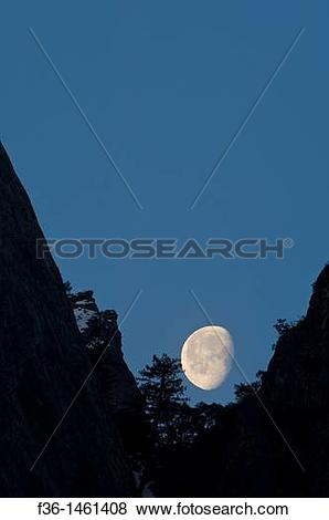Pictures of Waning gibbous moon setting behind mountain cliff.