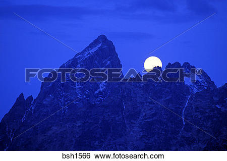 Stock Images of Full moon setting behind the Grand Teton at dawn.