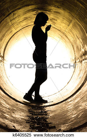 Stock Image of Silhouette of a young girl smoking in sewer pipe.