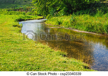 Stock Photos of stream shallow river around green trees and grass.