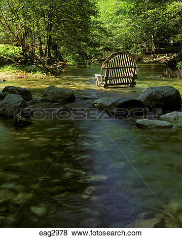 Pictures of An outdoor CHAIR or COUCH made of willows sits.