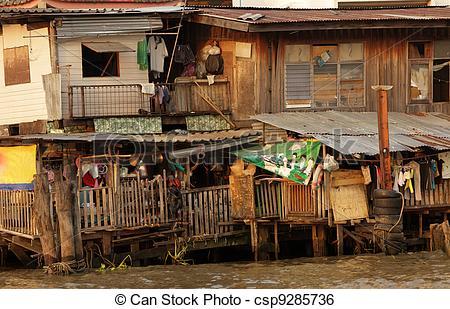 Stock Image of wooden shanty house on Bangkok riverbank, Thailand.