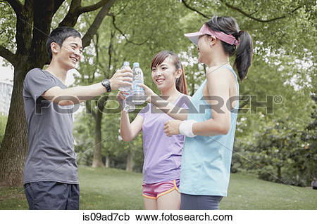Stock Photography of Jogger friends sharing water in park.