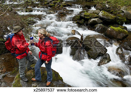 Picture of Young couple standing on rock by waterfall sharing.
