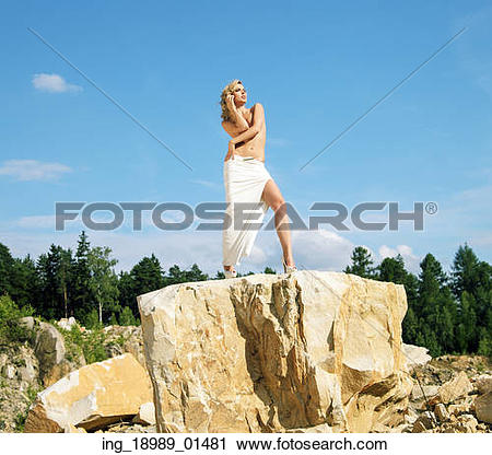 Stock Photography of Blonde posing on the giant and sharp rock.