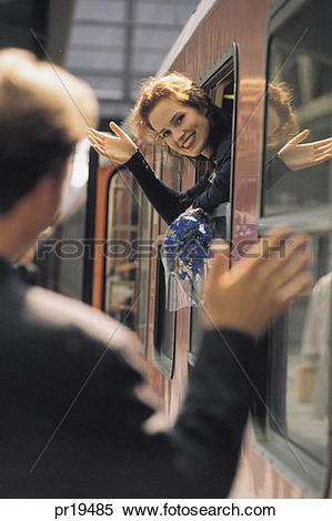 Stock Image of WOMAN WAVING TO MAN AS SHE LEAVES ON A TRAIN.