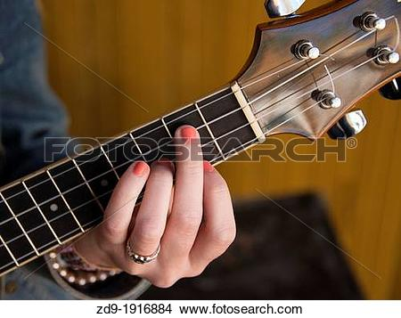 Stock Photo of A teenage girls painted nails as she forms a guitar.