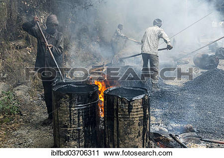 """Stock Photography of """"A worker heating tar in barrels with an open."""
