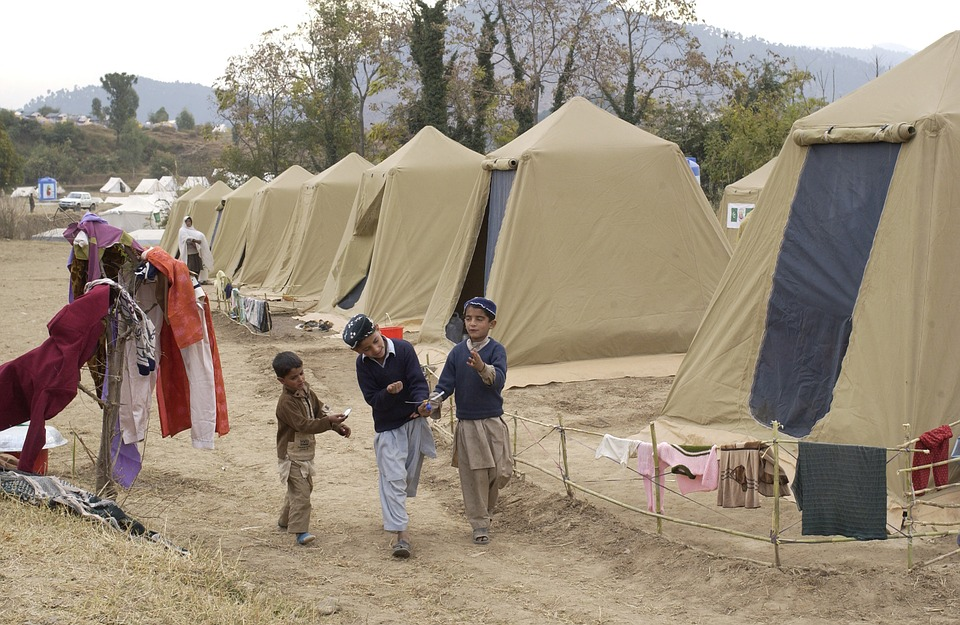 Free photo Tents Children Trees Pakistan Shinkiari Camp.