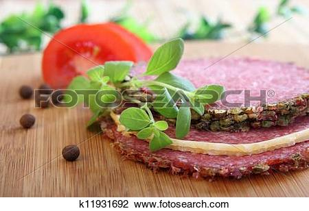 Stock Photo of salami slices and tomato with Marjoram herbs, short.