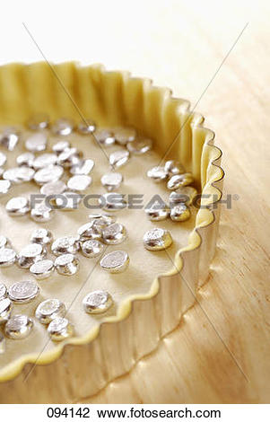Stock Photo of shortcrust pastry in mould filled with lead beans.