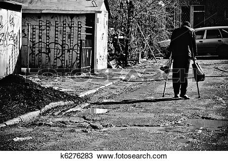 Stock Photo of A sick poor man with crutches walking down the.
