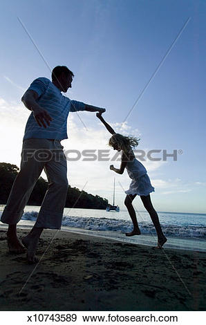 Stock Photograph of Silhouette of couple holding hands on beach.