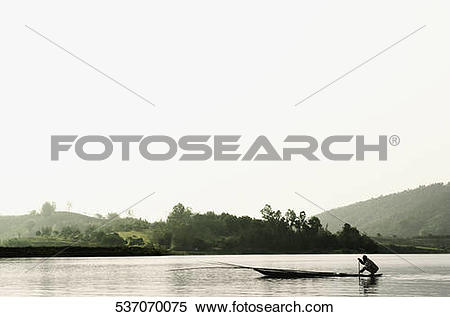 Stock Image of Silhouette of a person rowing a boat, Chiang Rai.