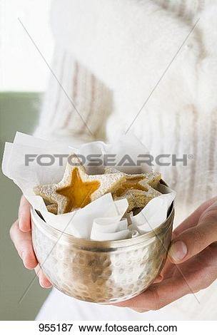 Picture of Hands holding jam biscuits in silver bowl 955187.