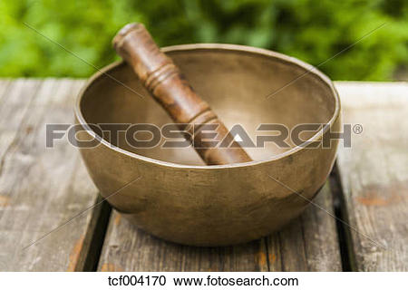 Stock Photography of Singing bowl on wooden terrace tcf004170.