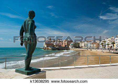 Stock Image of Statue of a naked woman against Sitges town view.
