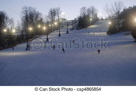 Stock Photo of night time skiing and snowboarding at a small ski.