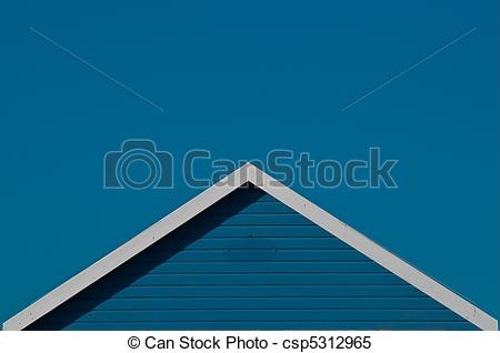 Stock Images of blue beach hut roof against blue sky.