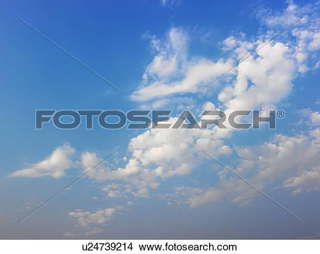 Stock Photo of Skyscape of blue sky and white fluffy clouds.