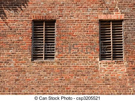 Stock Photography of Two Wood Slat Windows on Old Brick Wall.