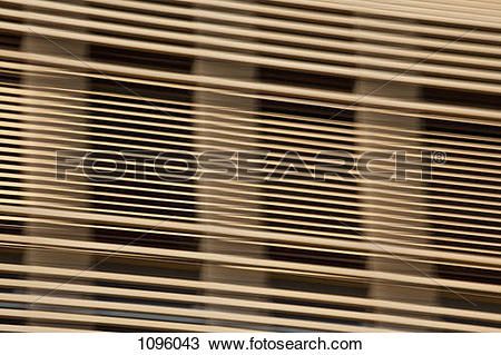 Stock Photo of Louvered wooden slats in front of window 1096043.