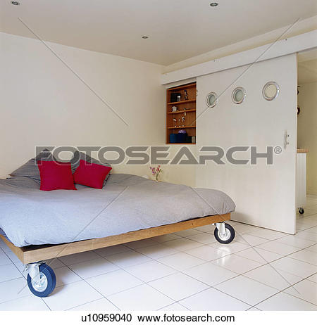 Stock Photography of Red cushions on bed with casters in modern.