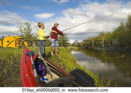 Stock Photo of Father teaching son to fish along Rabbit Slough in.