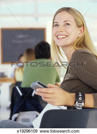 Stock Photograph of Young woman holding mobile phone in class.