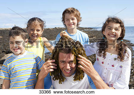 Stock Images of Portrait of smiling kids holding seaweed over.