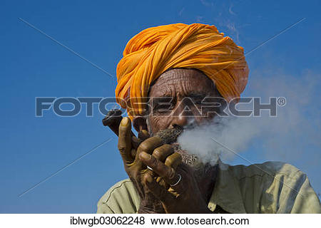 "Pictures of ""Elderly Rajasthani man with an orange turban smoking."