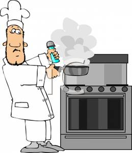 Chef Holding A Smoking Pan Over A Stove.