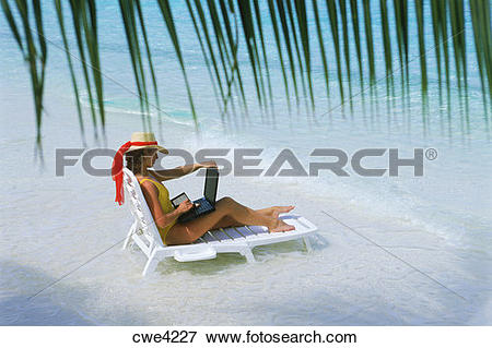 Picture of Woman sitting on sandy shore in beach chair with laptop.