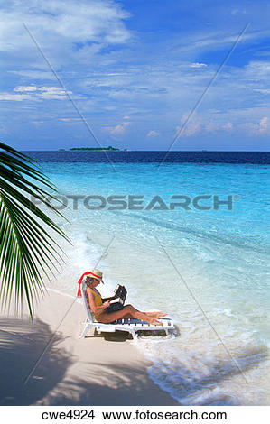 Stock Photo of Woman sitting on sandy shore in beach chair with.