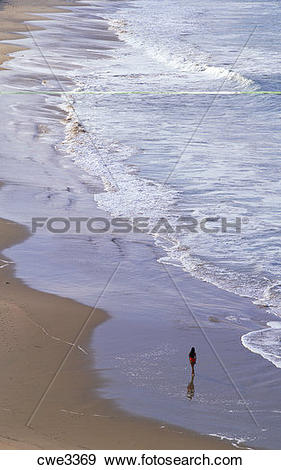 Stock Photograph of Woman running alone along sandy shore in.
