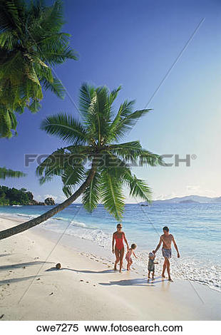 Stock Image of Family of four walking along sandy shore on La.