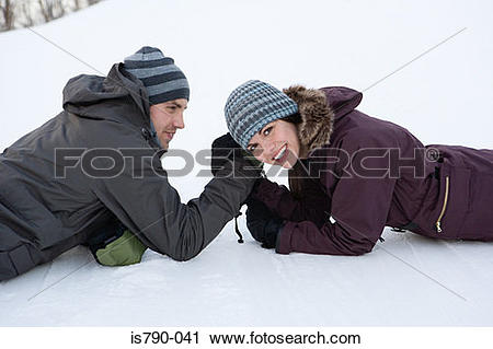 Stock Photography of Couple arm wrestling in snow is790.