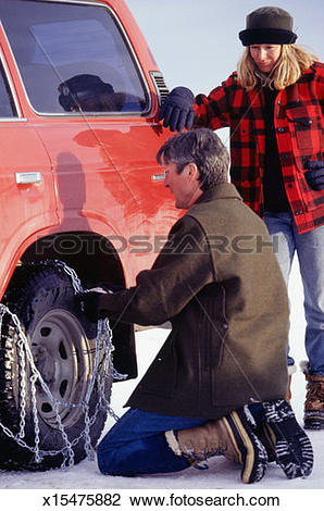 Stock Photo of Man putting snow chains on car tire x15475882.