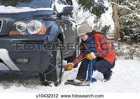 Stock Photo of Woman Putting Snow Chains Onto Tyre Of Car.