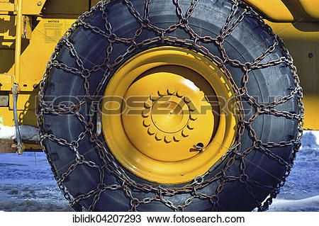 Stock Photo of Large Excavator tires with snow chains in winter.