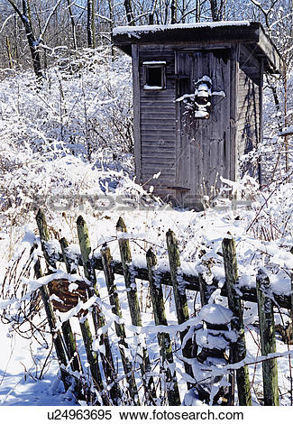 Stock Image of Winter: outhouse in snow, fence in foreground.