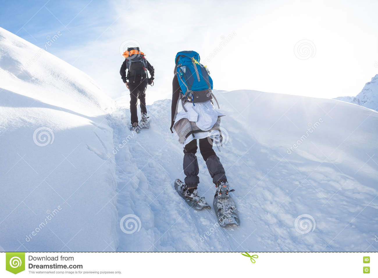 Man And Woman Hiking With Snow Shoes Through The Mountains Stock.