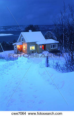 Stock Photo of Evening lights from snowbound home on long winter.