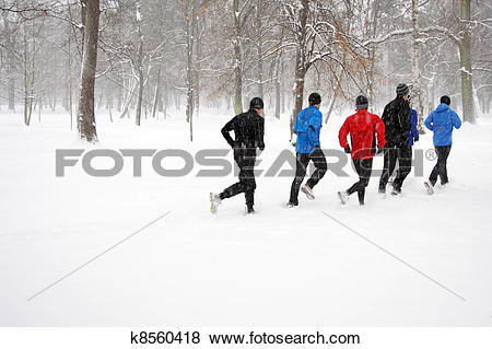 Pictures of Young people running in snowy park k8560418.