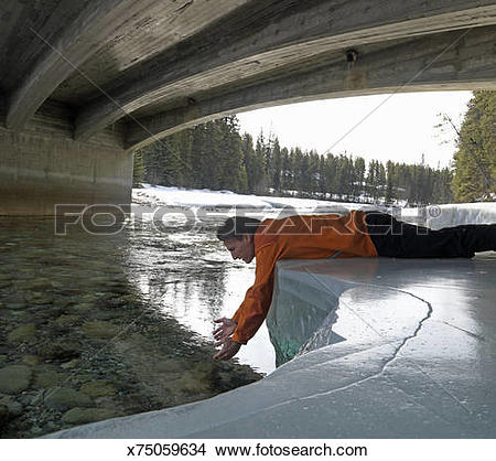 Stock Photo of Man lying on snowy riverbank, scooping for water.
